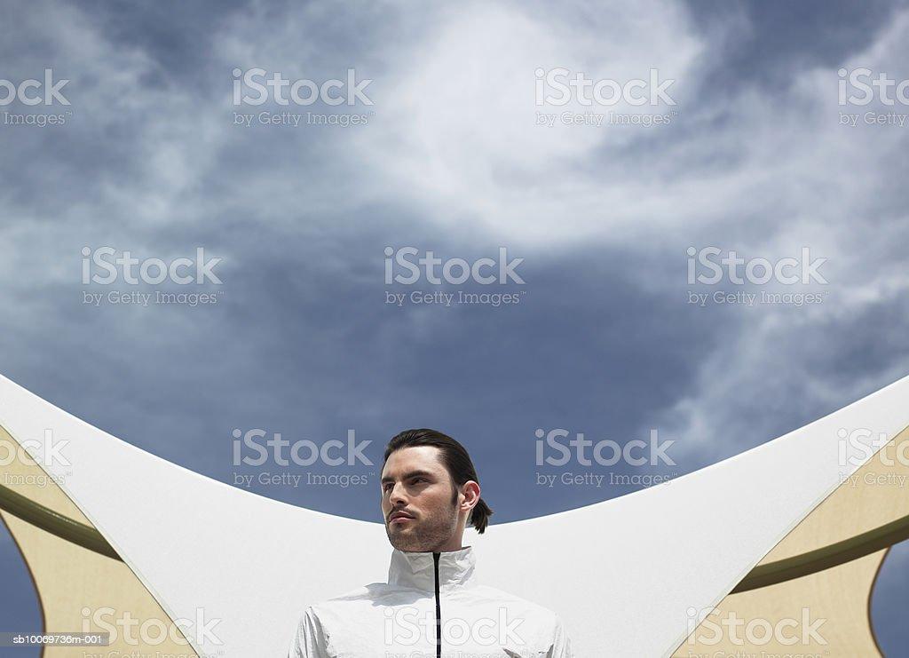 Young man standing en frente del edificio, vista de ángulo bajo foto de stock libre de derechos