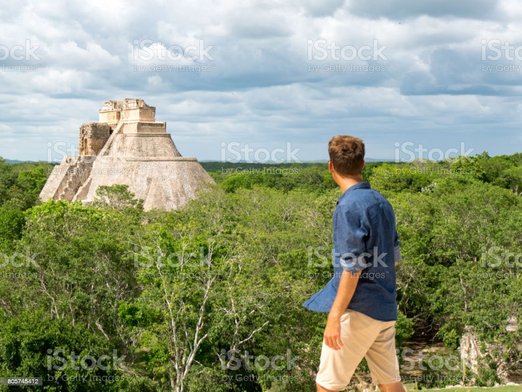 Young man standing in front of Uxmal temple, mexico stock photo
