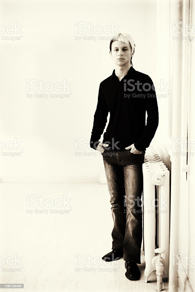 Young Man Standing in Room, Toned royalty-free stock photo