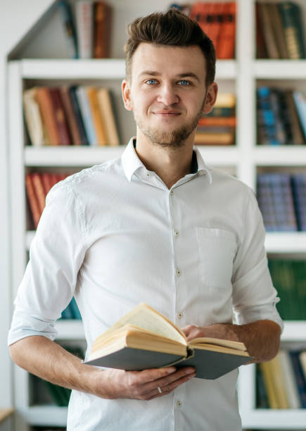 Young man standing in the library stock photo
