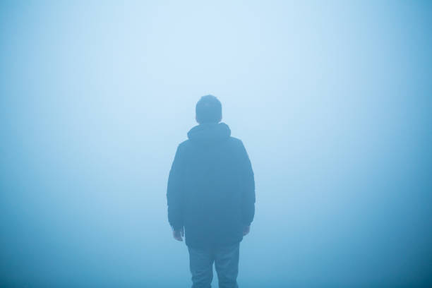 young man standing in the mist stock photo