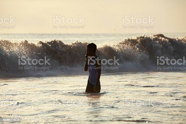 young man standing in water on the beach