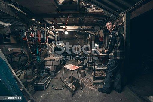 Young man standing inside dark messy barn.