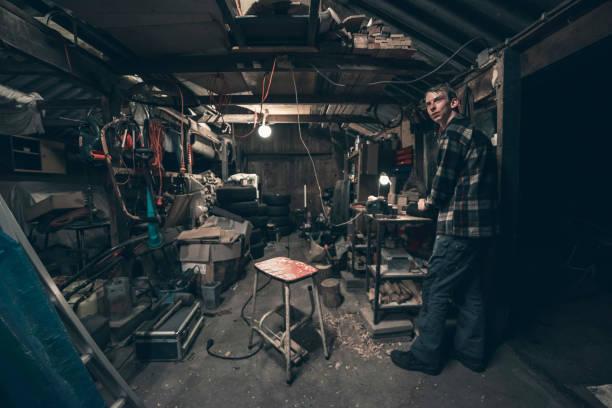 junger mann stehend in dunklen chaotisch scheune. - schuppen türen stock-fotos und bilder