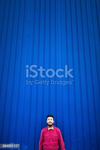 istock Young man standing looking up with blue background 534001127