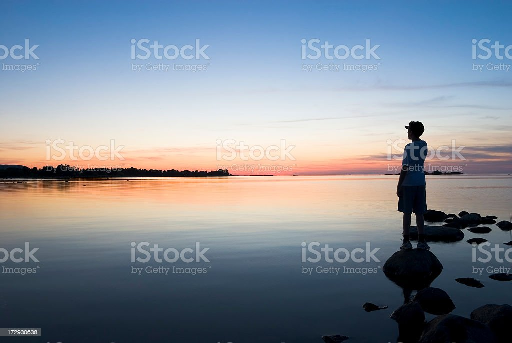 Young man standing on a lakeshore at sunset looking beyond stock photo