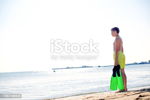 Young man with a swimming fin standing on a seashore