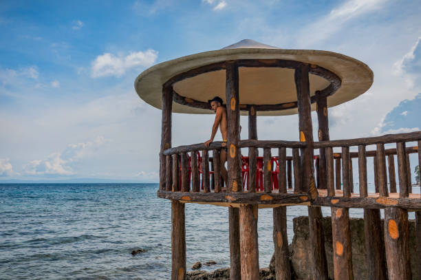 A young man standing on an outdoor terrace over the sea in Oslob, Philippines stock photo