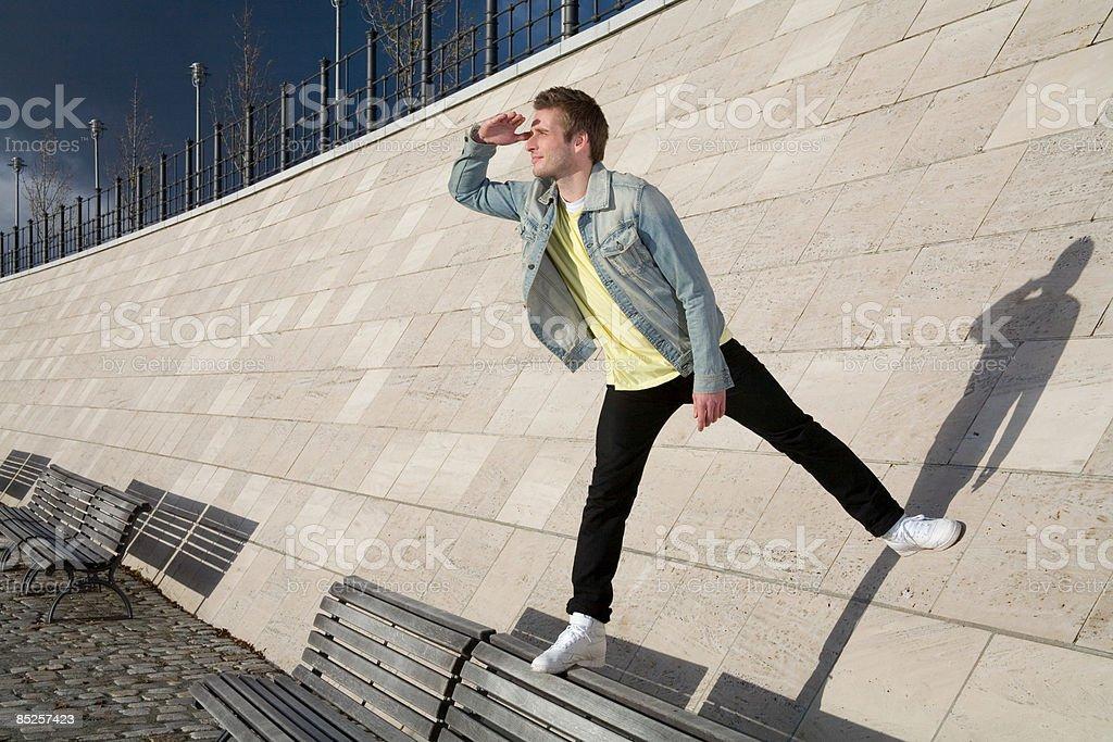 Jeune homme debout sur un banc et mur photo libre de droits