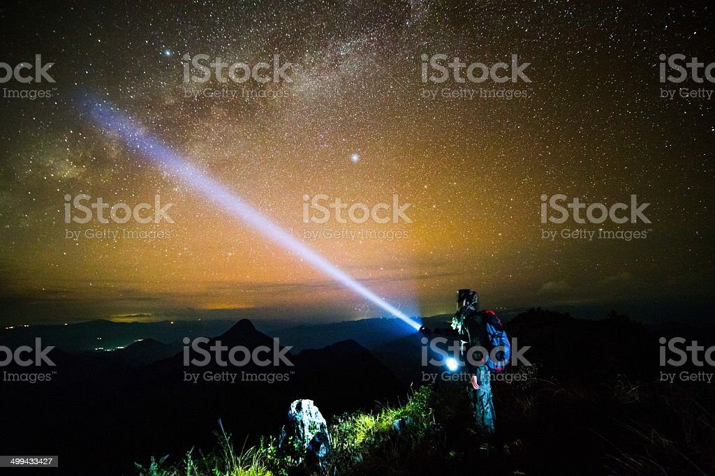 Young man Standing on Mountain with night sky stock photo