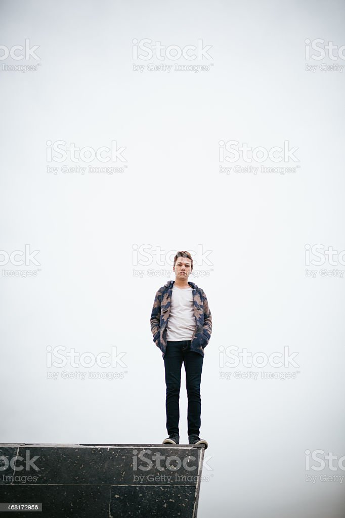 Young man standing on stone block Young man standing on stone block. 20-24 Years Stock Photo