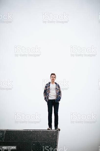 Young Man Standing On Stone Block Stock Photo - Download Image Now
