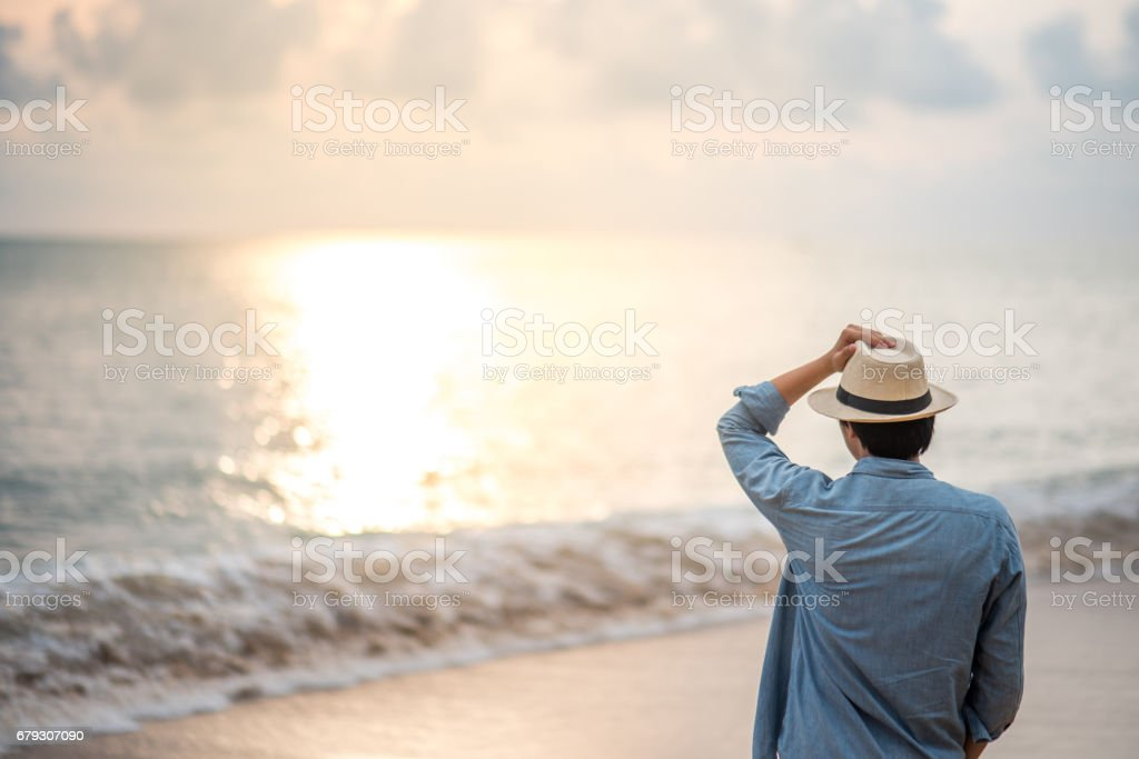 Young man standing on the beach and see beautiful sunset royalty-free stock photo