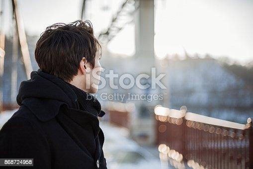 istock Young man standing on the bridge 868724958