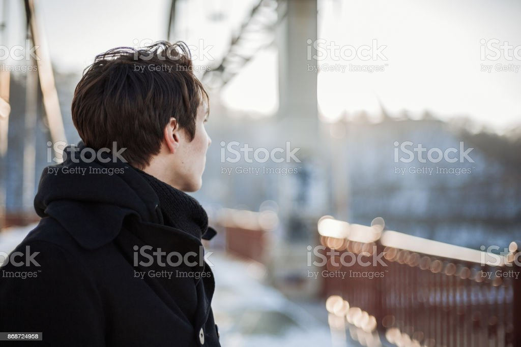 Young man standing on the bridge stock photo