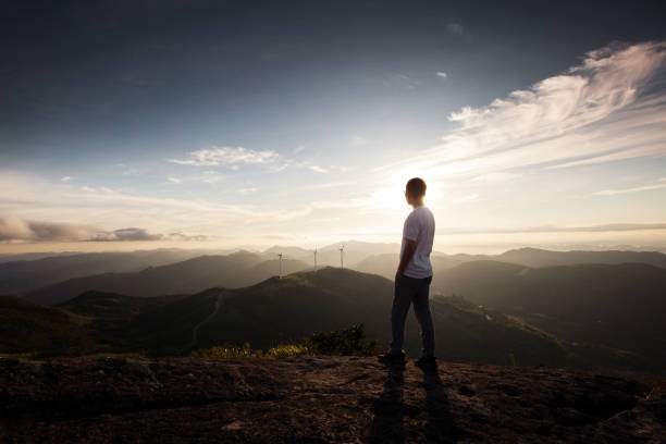 Young man standing on top of cliff in summer mountains at sunrise stock photo