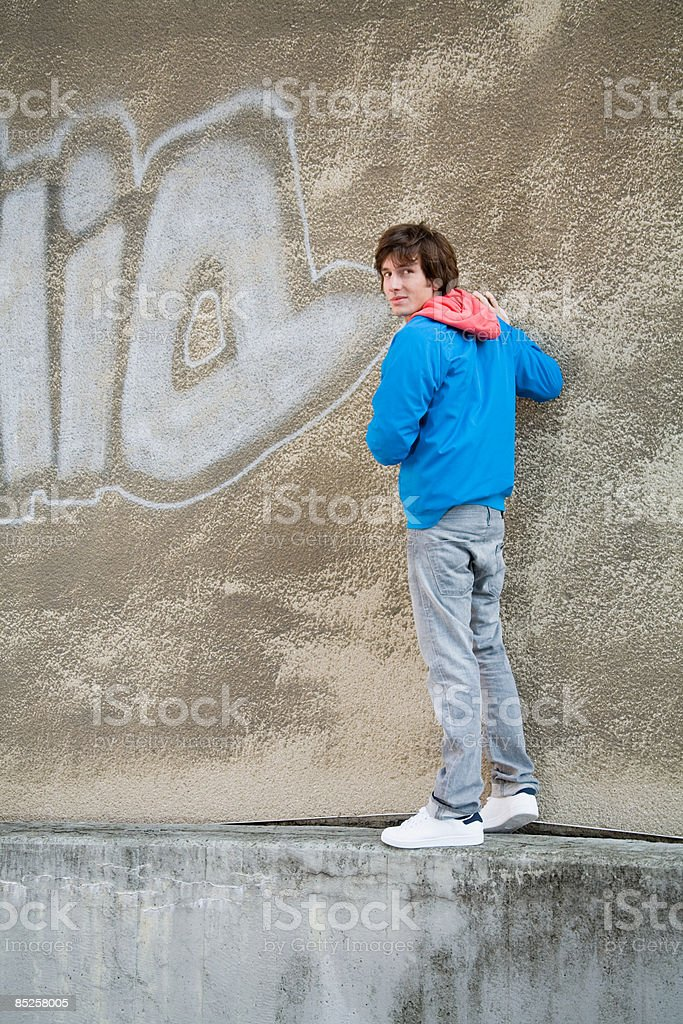 Young man standing on wall royalty-free stock photo