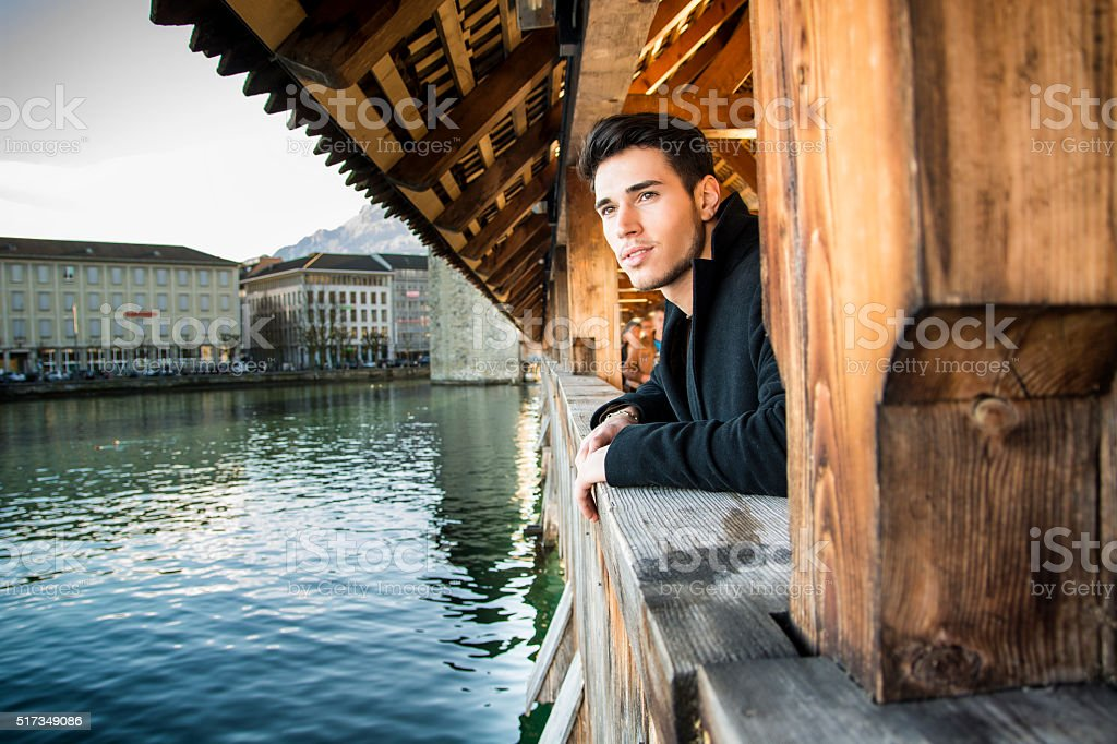 Young man standing on wooden footbridge in Switzerland while looking stock photo