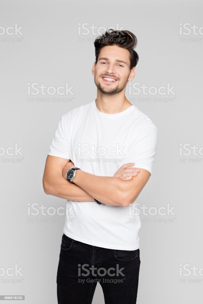 Young man standing relaxed Portrait of young man standing with his arms crossed on grey background 25-29 Years Stock Photo