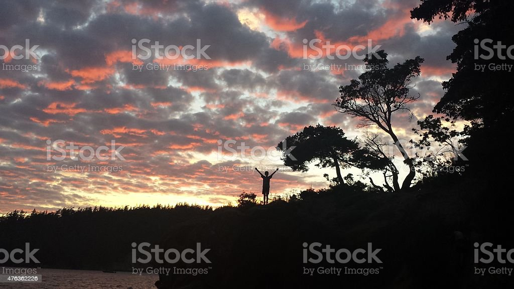 Young Man Standing Triuphant  Cliffside at Sunset in Silhouette stock photo
