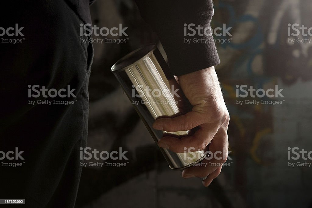 Young man standing with a silver spray can in his hand stock photo