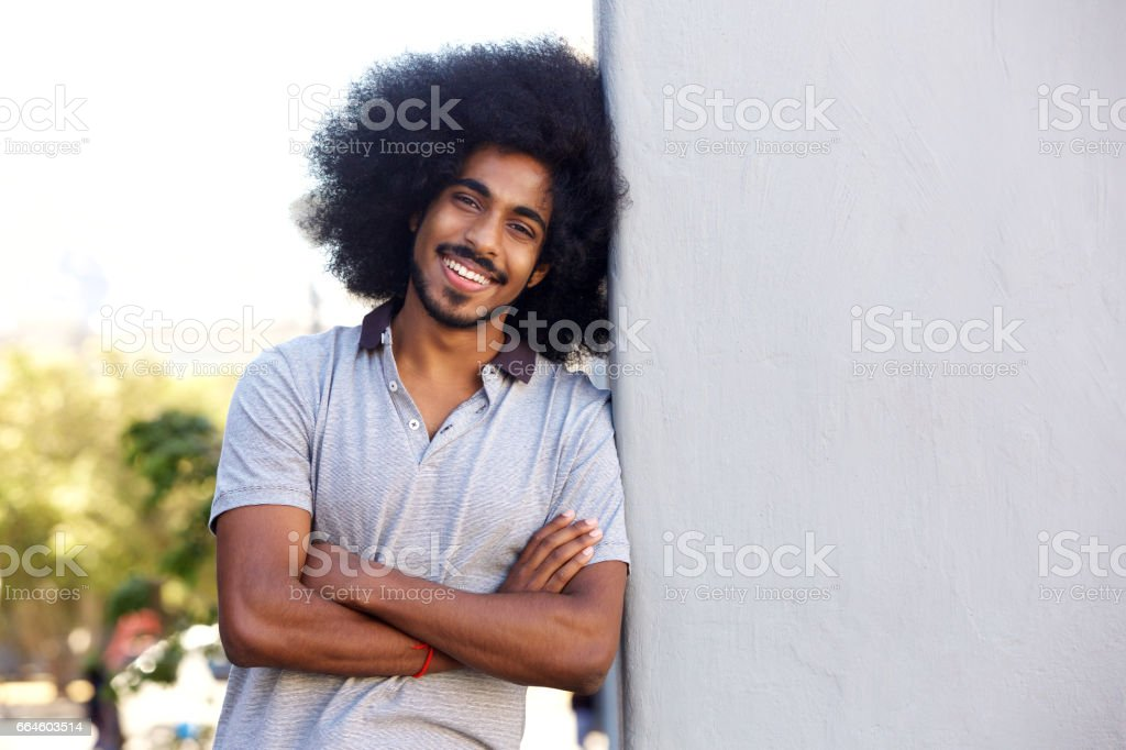 young man standing with arms crossed leaning on white wall stock photo
