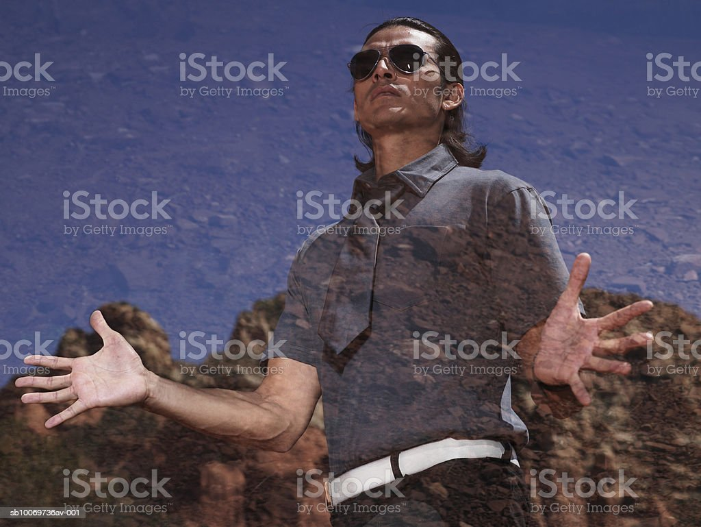 Young man standing with arms out, low angle view royalty-free stock photo