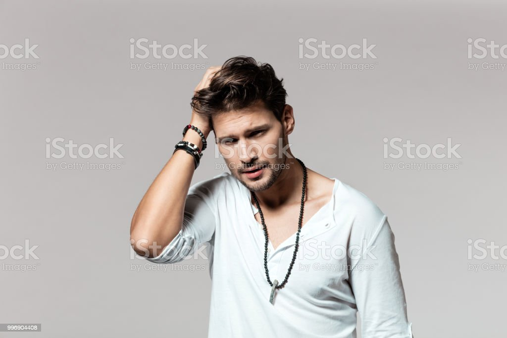Young man standing with hands on head Portrait of young caucasian man standing with hands on head over grey background 25-29 Years Stock Photo