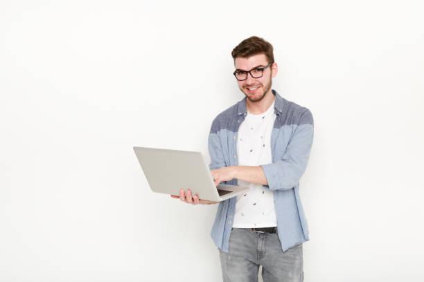 Jovem de pé com laptop - foto de acervo