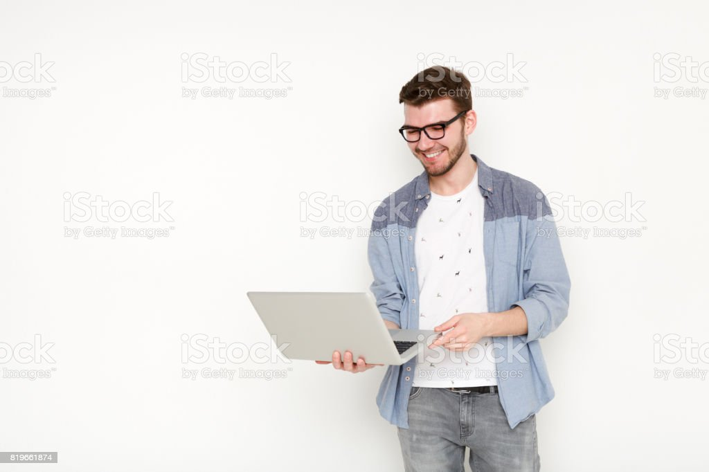 Young man standing with laptop stock photo