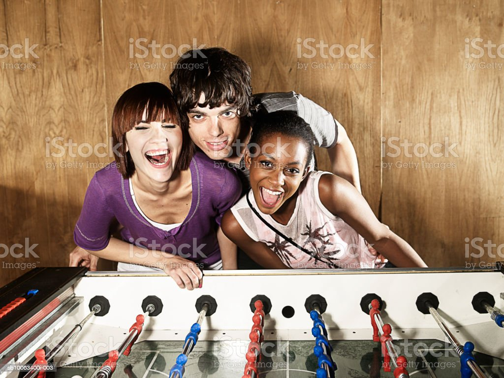 Young man standing with two women by table football game, portrait royalty-free stock photo
