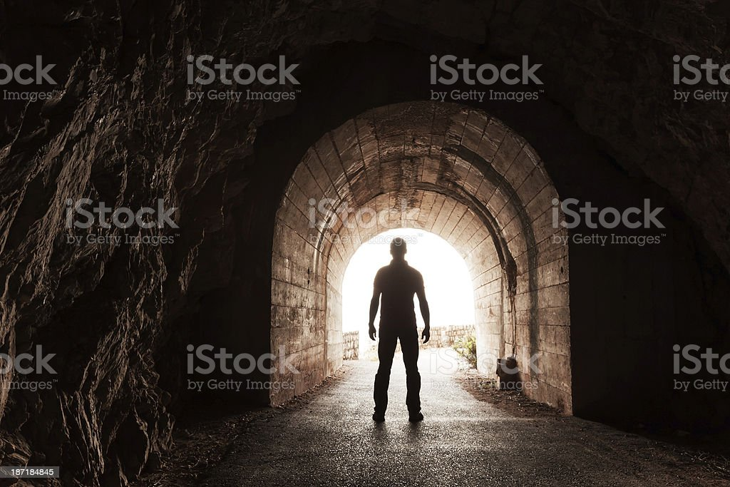 Young man stands in dark concrete tunnel stock photo