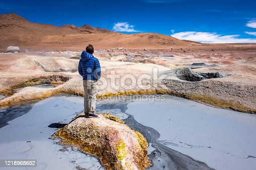 Young man stands on a tiny sulfur island with muddy lake around. Geothermal area named Sol de Manana in Bolivian Altiplano