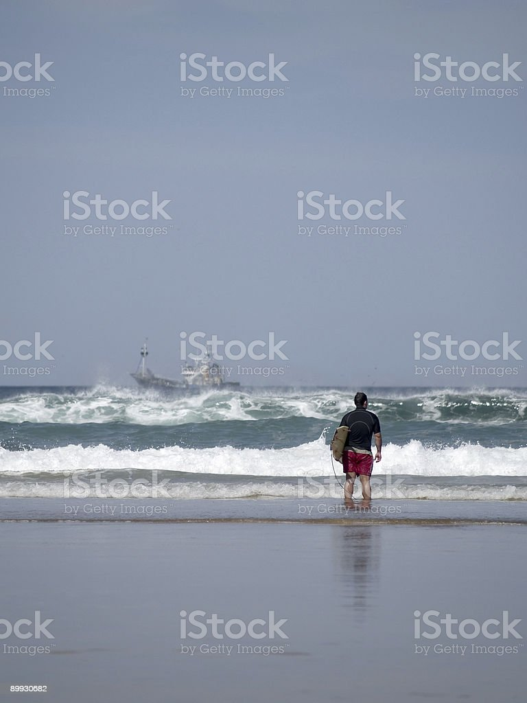 Young Man Stands On The Coastline Checking Surf Conditions