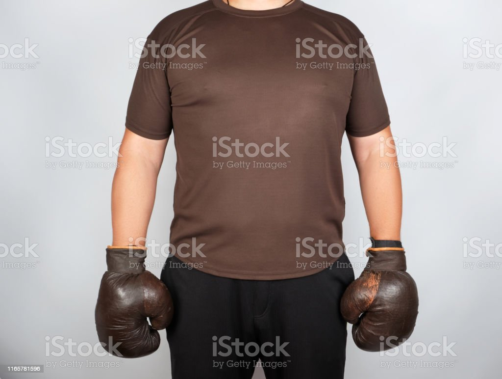 young man stands wearing very old vintage brown boxing gloves on his...