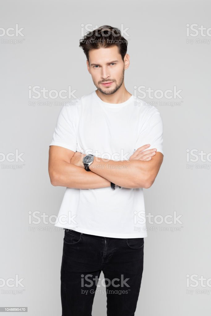 Young man staring at camera Portrait of handsome man standing with arms crossed and staring at camera on grey background 25-29 Years Stock Photo