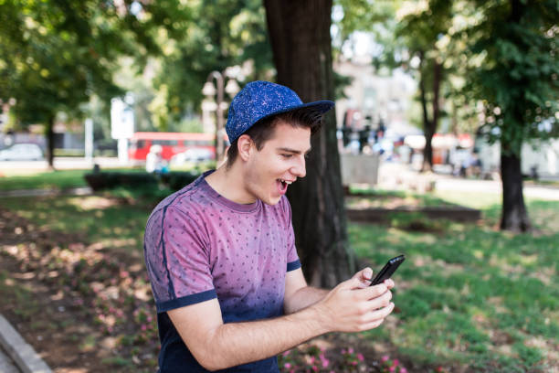 young man starting his adventure in new video game - mobile game stock photos and pictures
