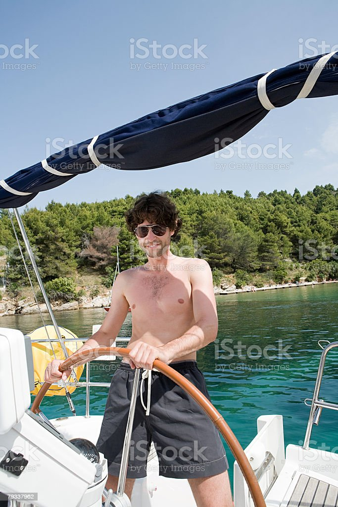 A young man steering a yacht royalty-free 스톡 사진