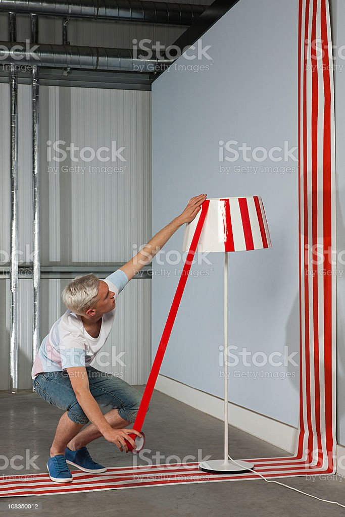 Young man sticking red adhesive tape to lampshade stock photo
