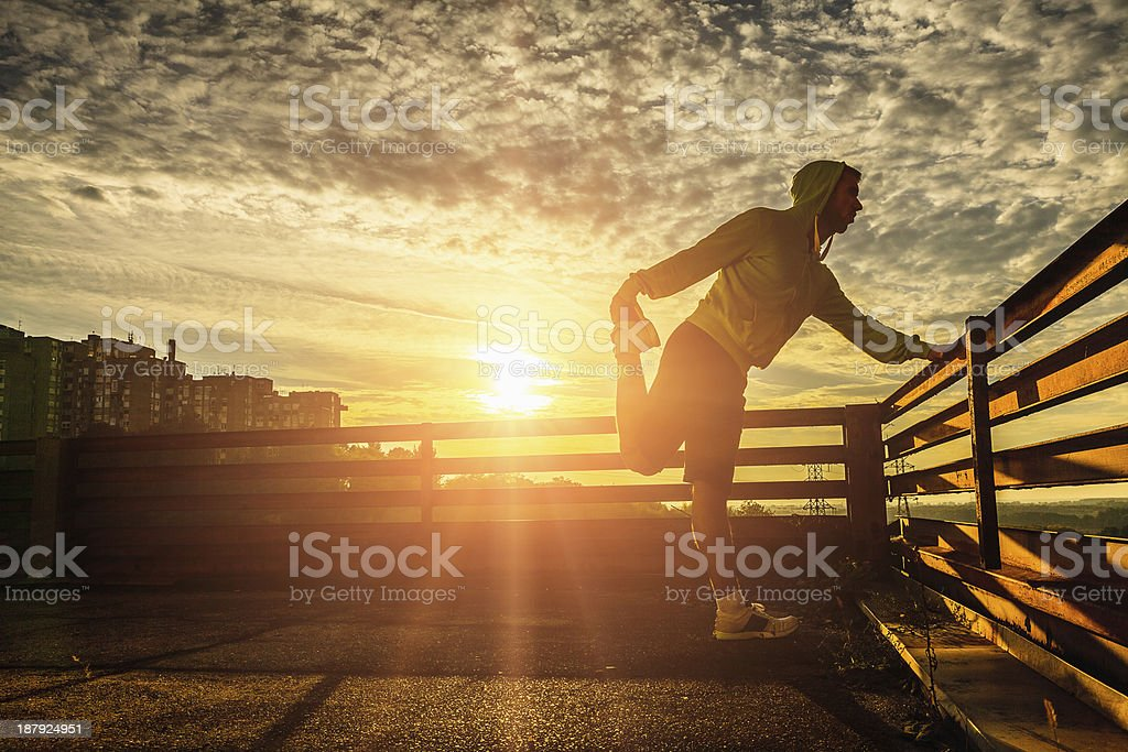 Young man stretching after running at sunset stock photo