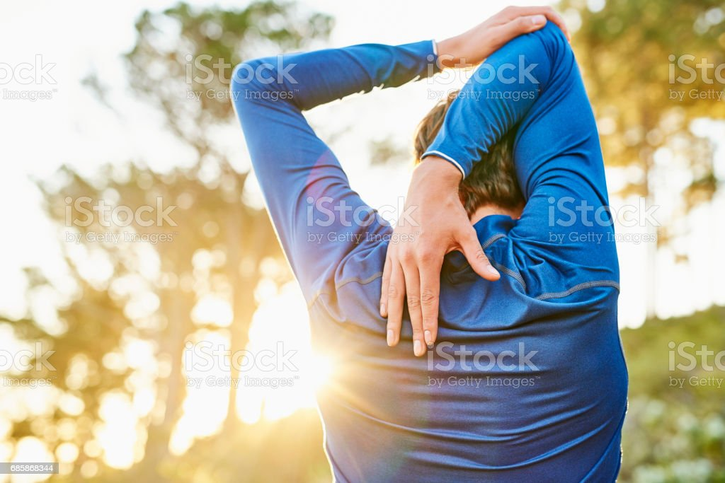Young man stretching arm and shoulder outdoors stock photo