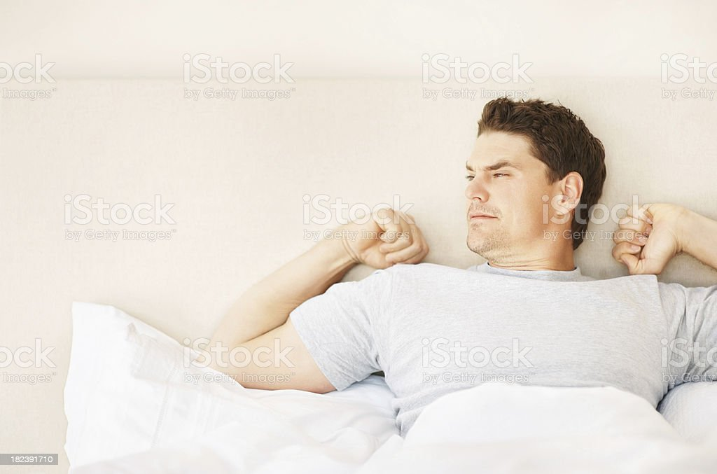 Young man stretching arms on waking up royalty-free stock photo