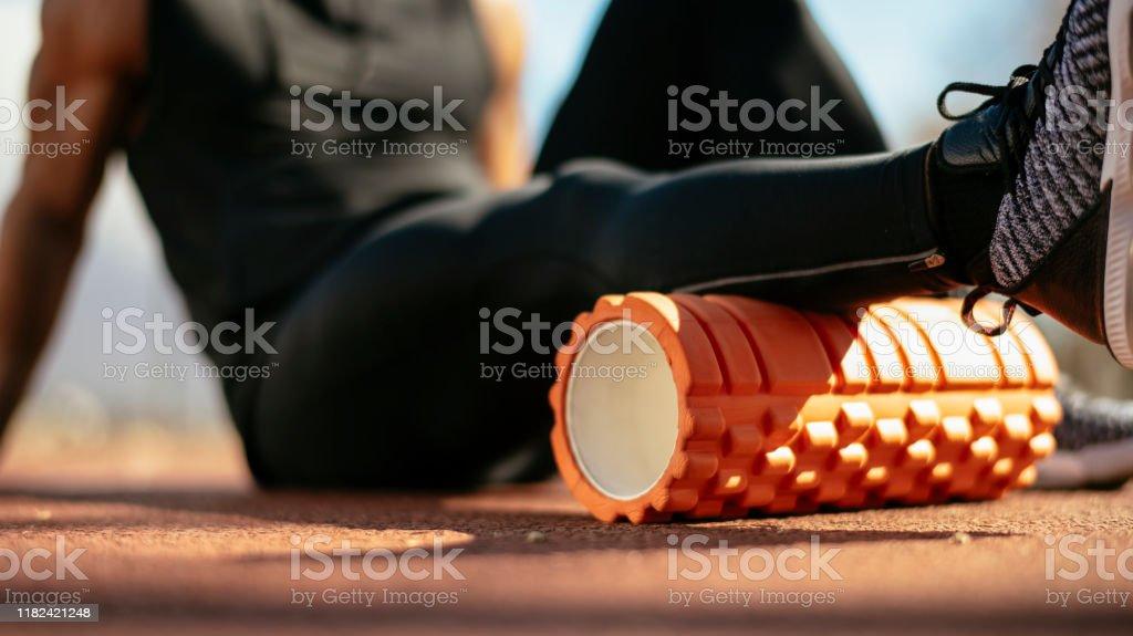 Junger Mann streckt sich auf einer Schaumstoffwalze - Lizenzfrei Aktiver Lebensstil Stock-Foto