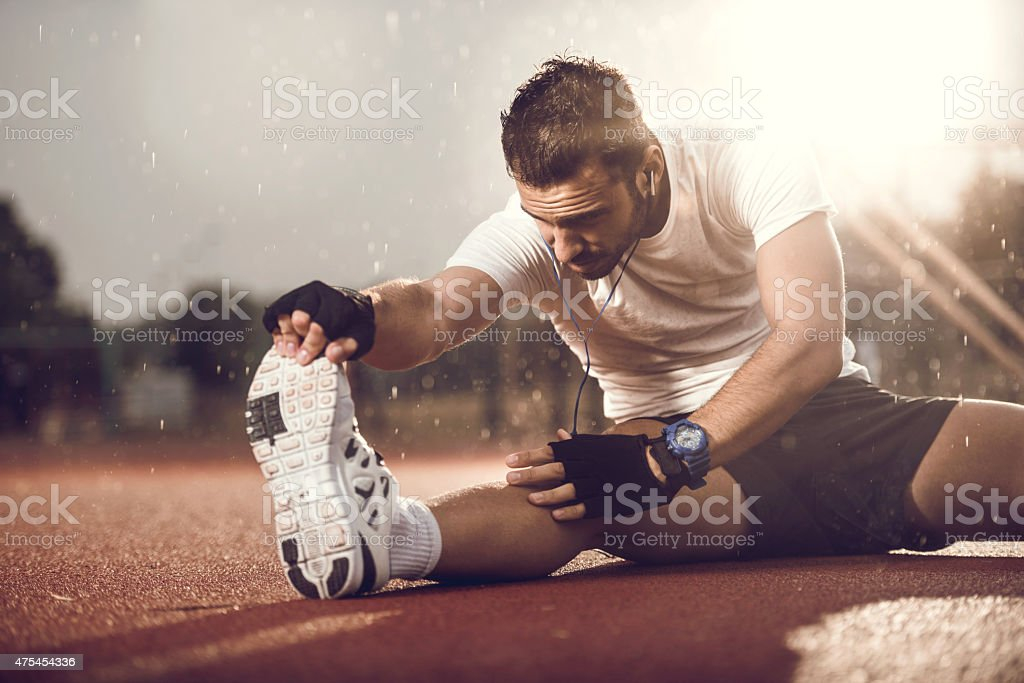Young man stretching his leg on a rain. stock photo