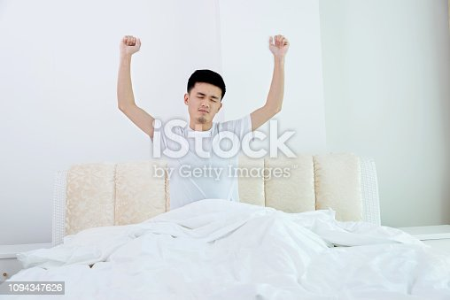 Young man stretching in bed.