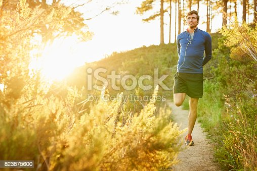Full length of young man stretching leg on mountain footpath. Male athlete is warming up before jogging. He is in sportswear.