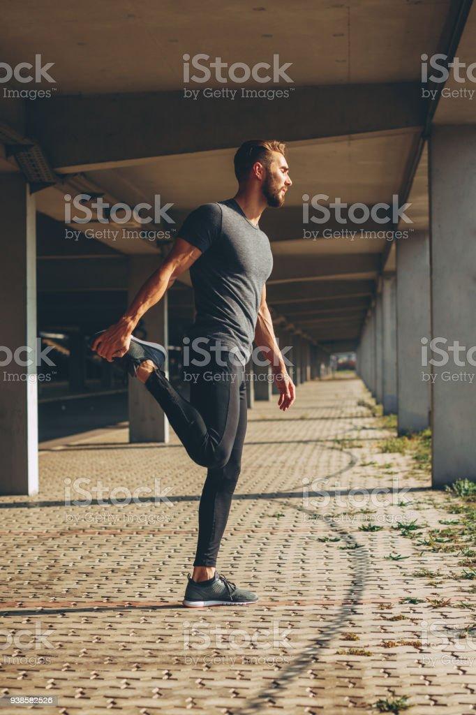 Junger Mann stretching Beine im städtischen Umfeld – Foto