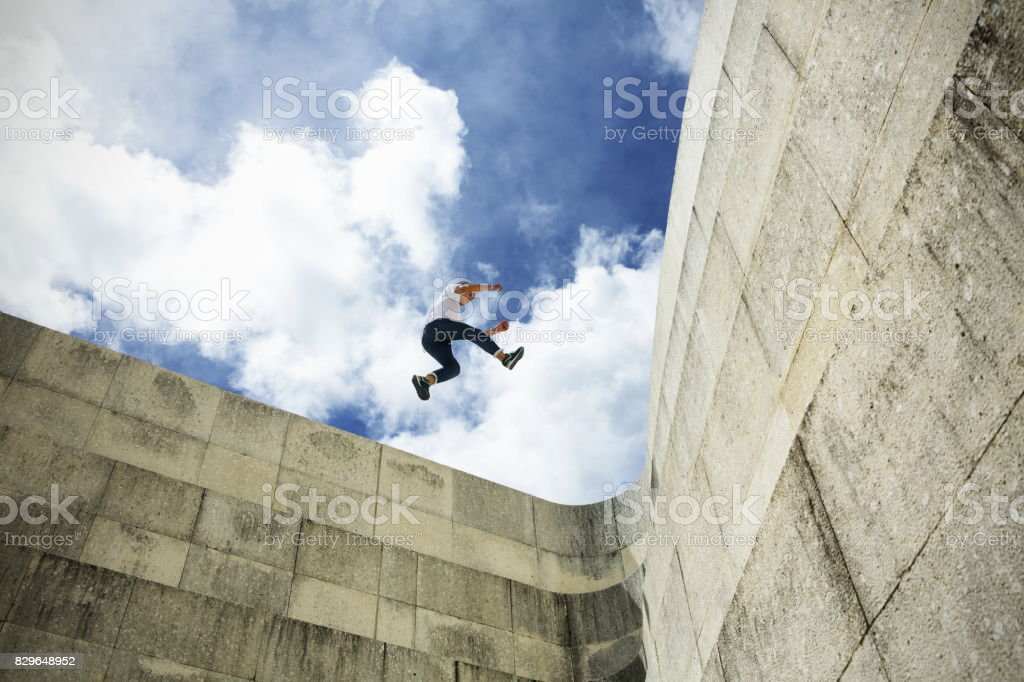 Young man stride jumping  on concrete wall stock photo