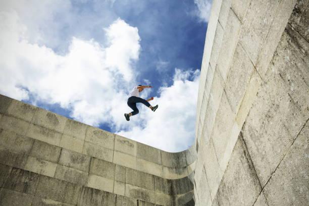 junger mann schritt springen auf betonwand - mobilität stock-fotos und bilder