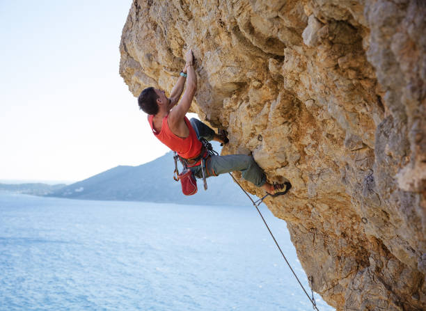 Young man struggling to climb overhanging cliff stock photo